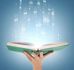 education and book concept - close up hand holding open book with magic lights