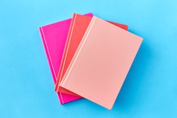 education and object concept - notebooks or books on blue background