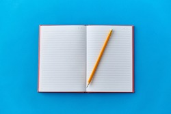 education and object concept - open notebook or diary with pencil on blue background
