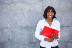 Education and people concept. Happy smiling African American student girl with workbook, standing outdoors, looking at camera on the gray background.
