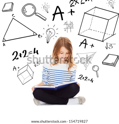 education and school concept - little student girl studying and reading book