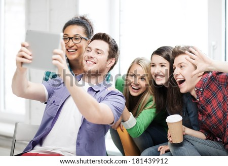 education and technology concept - group of students making picture with tablet pc at school #181439912
