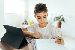 Education and technology concept - student boy with tablet computer learning at home