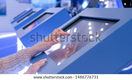 Education and technology concept - woman using interactive touchscreen display of electronic kiosk at technology exhibition #1486776731