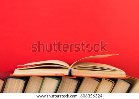 education and wisdom concept - open book on wooden table, red background #606356324