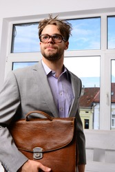 Education and work concept. Serious man or professor, teacher or worker with beard and messy hair in nerd glasses. Man with briefcase on glass door background. Nerd or brainiac wearing classic jacket