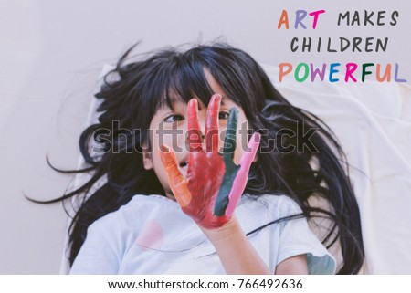 Education , Art and creativity learning concept - A black long hair asian student put her colourful hands painting up with art quote - Art makes children powerful