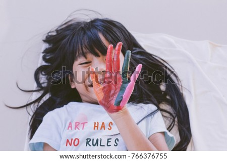 Education , Art and creativity learning concept - A black long hair asian student wearing ART HAS NO Rules T- shirt and put her colourful hands painting up