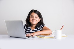 Education at home concept - Cute little Indian/Asian girl studying or completing home work on study table with pile of books, educational globe, laptop computer, coffee mug etc