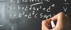 Education background concept. Close up male hand writing mathematical formula on chalkboard.