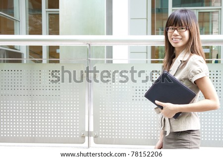Education / Business woman passing by office building - stock photo