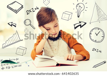 education, childhood, people, homework and school concept - bored student boy reading book or textbook at home over mathematical doodles