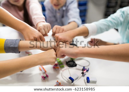 education, children, technology, science and people concept - group of happy kids with building kit making fist bump at robotics school #623158985