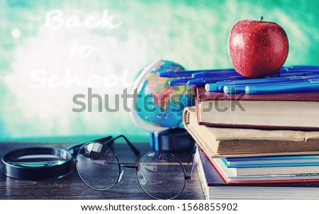 Education concept. A stack of textbooks and a book on the desk with glasses and computer. School breakfast apple and homework.
