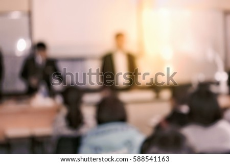 Education concept, blurred students studying in classroom with team teachers using screen and projector for showing information #588541163