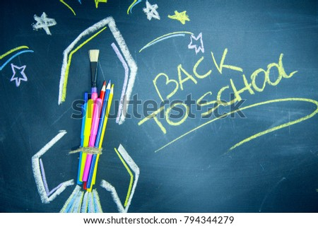 Education concept: Creative learning. Space rocket ship made of colored pencils on a black chalkboard and Back To School inscribed with a yellow chalk #794344279