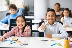 Education Concept. Diverse group of happy smiling international classmates sitting at desk in classroom and showing thumbs up sign gesture, girl and boy enjoying studying at school