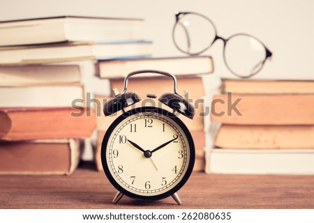 Education concept. Eyeglasses with Alarm clock with old books on table . Vintage filter