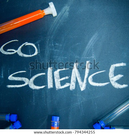 Education concept: Go Science inscribed with colored chalks on a black chalkboard and chemistry flasks, top view, close up, square crop #794344255