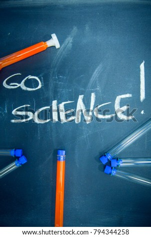 Education concept: Go Science inscribed with colored chalks on a black chalkboard and chemistry flasks, top view, close up #794344258