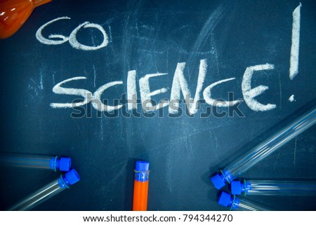 Education concept: Go Science inscribed with colored chalks on a black chalkboard and chemistry flasks, top view, close up #794344270