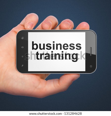 Education concept: hand holding smartphone with word Business Training on display. Generic mobile smart phone in hand on Dark Blue background.