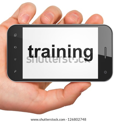 Education concept: hand holding smartphone with word Training on display. Generic mobile smart phone in hand on White background.