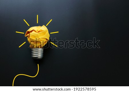 Education concept image. Creative idea and innovation. Crumpled paper as light bulb metaphor over black background