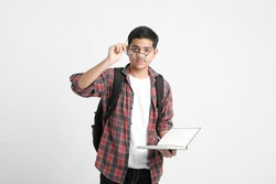 Education concept : Indian college student holding books in hand and standing on white background