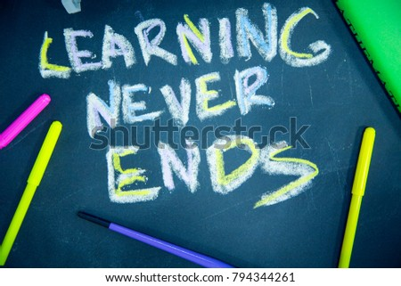 Education concept: Learning Never Ends inscribed with colored chalks on a black chalkboard and pencils, top view #794344261