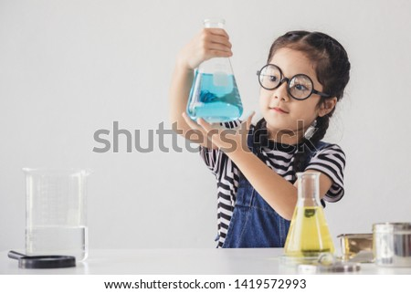 Education concept - Little scientists children is looking at erlenmeyer flask containing chemicals to perform experiments in the laboratory, Beaker on the side table.
