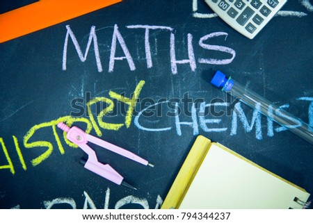 Education concept: Names of school subjects inscribed on a black chalkboard with colored chalks and stationary, close up, top view #794344237