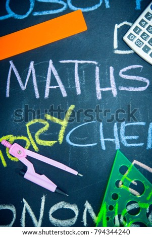 Education concept: Names of school subjects inscribed on a black chalkboard with colored chalks and stationary, close up, top view #794344240