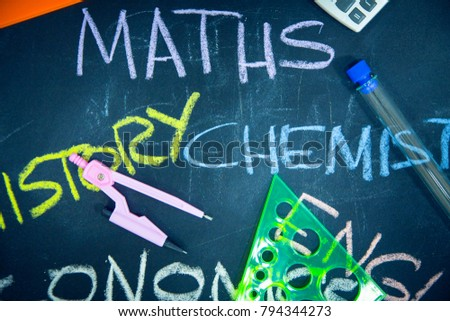 Education concept: Names of school subjects inscribed on a black chalkboard with colored chalks and stationary, close up, top view #794344273