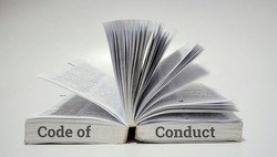 Education concept. Open book and word code of conduct on white background