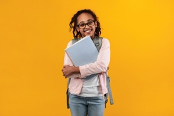 Education Concept. Portrait of positive smiling African American girl wearing glasses and backpack holding textbooks, posing and looking at camera isolated on yellow studio background