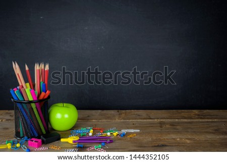 Education concept. Stationery various types were placed on the table, a chalkboard background with space to add text, images, prepared in advertising. Green Apple is a component.
