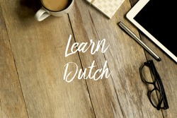 Education concept. Top view of tablet, glasses. notebook pen and a cup of coffee with LEARN DUTCH on wooden background.is a West Germanic language   widely used in  Netherlands and Belgium in 2017