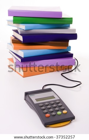 Education cost concept - POS terminal with a stack of colorful books (focus on the POS)