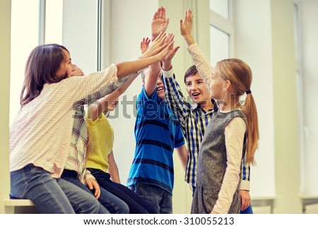 education, elementary school, children, gesture and people concept - group of smiling school kids making high five in corridor Foto stock ©