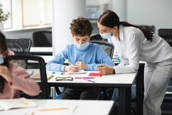 Education, Elementary School, Learning and People Concept. Female teacher in disposable protective mask helping small school boy who sitting at desk in classroom, standing near table, explaining task