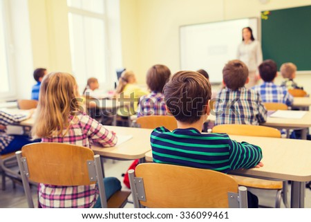 education, elementary school, learning and people concept - group of school kids sitting and listening to teacher in classroom from back Photo stock ©
