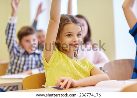 education, elementary school, learning and people concept - group of smiling school kids sitting in classroom