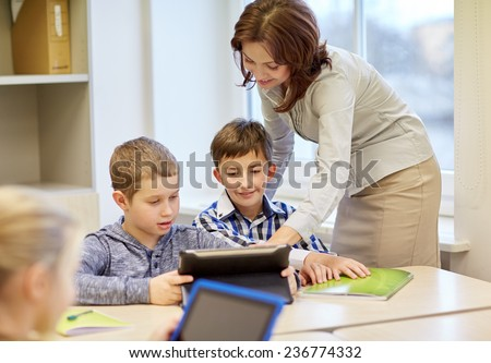 education, elementary school, learning and people concept - teacher helping school kids with tablet pc computer in classroom