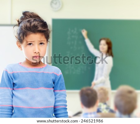 education, elementary school, people, childhood and emotions concept - sad little student girl over green chalk board background