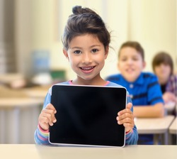 education, elementary school, technology, advertisement and children concept - little student girl showing blank black tablet pc computer screen over classroom and classmates background