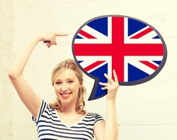 education, foreign language, english, people and communication concept - smiling woman holding text bubble of british flag and pointing finger