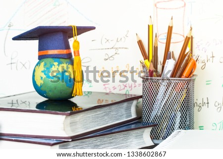 Education Graduate study concept: Graduation hat on pencils with formula arithmetic equation graph on near global model at university classroom. Ideas for knowledge learning success, Back to School