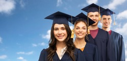 education, graduation and people concept - group of happy graduate students in mortar boards and bachelor gowns over blue sky and clouds background