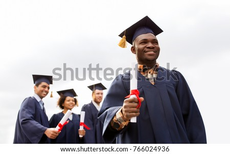 education, graduation and people concept - happy african american graduate in mortar boards and bachelor gown with diploma and group of international students